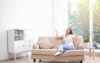 A young woman relaxing inside a home with air conditioning