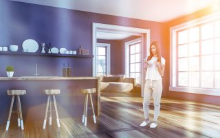 Woman in corner of modern kitchen with gray walls, wooden floor, gray and wooden bar with wooden stools, a shelf with plates and doorway to living room. Toned image