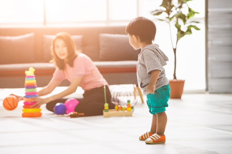 Happy Asian family, young beautiful mother in pink blouse, sitting on floor, playing with son, adorable little toddler boy in grey T-shirt, short, looking at mother in bright light living room